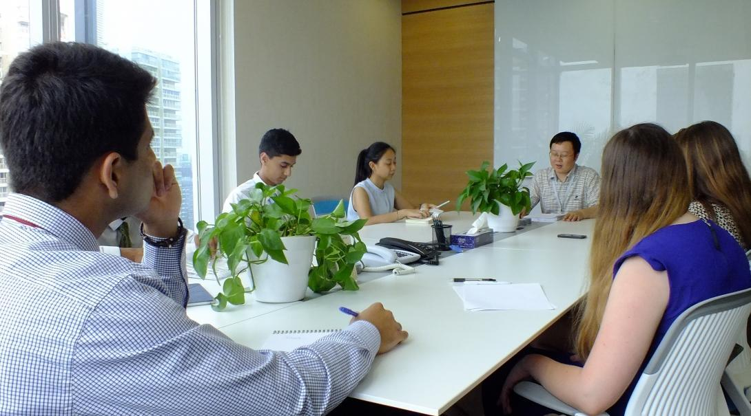 Business professionals working for a company in China involve teenage Projects Abroad interns in a meeting.